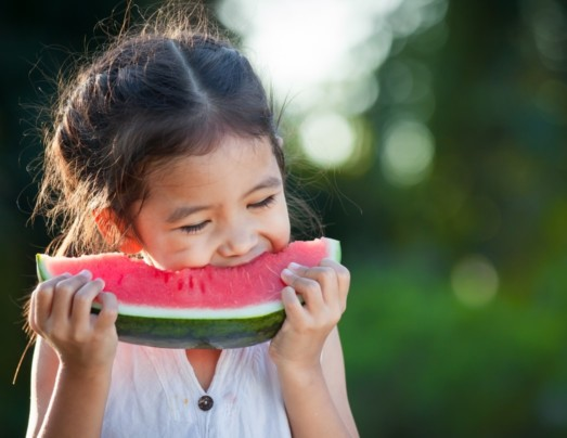 Young girl eating a slice of watermelon